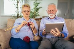 Senior woman knitting woollen clothes and her husband is using digital tablet royalty free stock photography