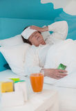 Senior woman laid ill in the bed with medicament and pillows, Stock Photography