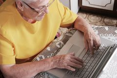 Senior woman with a laptop. Senior woman typing a message on a laptop Royalty Free Stock Photo