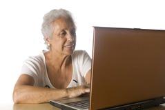 Senior woman on laptop. On white background Royalty Free Stock Photo