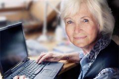Senior woman with laptop. Senior lady sitting on her workingplace, ready to start her laptop Royalty Free Stock Image
