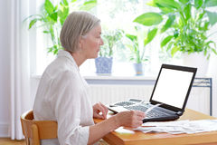 Senior woman laptop bills receipts. Senior woman at home with a calculator and lots of receipts in front of her laptop making her annual tax declaration, blank Royalty Free Stock Photography