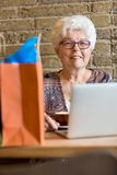 Senior Woman With Laptop In Coffeeshop Stock Photo