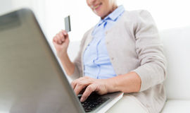 Senior woman with laptop and credit card at home Royalty Free Stock Photography