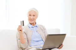 Senior woman with laptop and credit card at home Stock Image