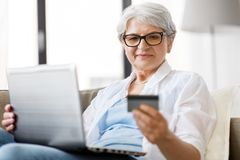 Senior woman with laptop and credit card at home stock images