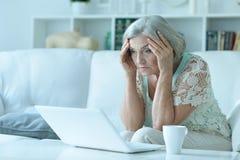 Senior woman with laptop. Portrait of a sad senior woman with laptop stock photos
