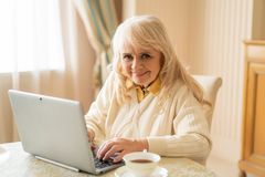 Senior woman at the laptop relaxing at home sitting at the table royalty free stock images