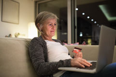 Senior woman with laptop sitting on the couch shopping online Royalty Free Stock Photos
