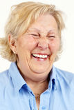 Senior woman laughing. Portrait of a blond senior woman laughing hysterically or giggling Royalty Free Stock Images