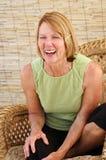 Senior Woman Laughing. Natural senior woman laughing in a natural interior Royalty Free Stock Photography