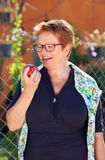Senior woman laughing as she holds a red apple Stock Photography