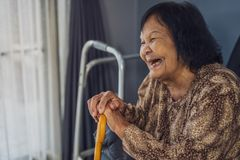 Senior woman laughing and holding wooden cane in living room. At home stock images