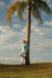 Senior woman leaning against palm tree Stock Images