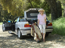 Senior woman leaning on car boot beside golf bag, smiling, portrait Royalty Free Stock Photo