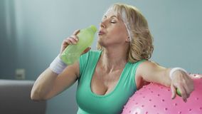 Senior woman leaning on fitness ball, drinking water after workout, hydration. Stock footage stock video