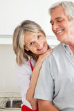 Senior woman leaning on man. Senior women in kitchen leaning on shoulder of man Stock Image
