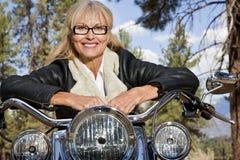Senior woman leaning on motorbike handlebars Royalty Free Stock Photography