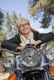 Senior woman leaning on motorcycle handlebars in a forest stock image