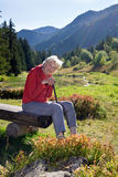 Senior woman leaning on walking steak in the mountains. Stock Photos