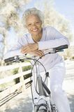 Senior Woman Leans On Handlebars Of Mountain Bike Royalty Free Stock Image