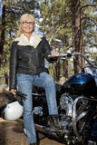 Senior woman in leather jacket poses with motorcycle Stock Photos