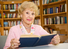 Senior Woman in Library. Beautiful senior woman studying in the library Royalty Free Stock Photo
