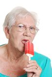 Senior woman licking a red popsicle Stock Photo