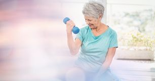 Senior woman lifting dumbbells in gym stock photography