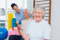 Senior woman lifting dumbbells while sitting with man and instructor Royalty Free Stock Images