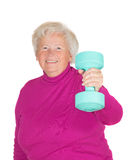 Senior woman lifting weights. Cheerful senior woman lifting weights holding up a dumbbell in her flexed arm in a health and fitness concept Stock Photo