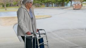 Senior woman in light jacket, walking with the assistance a walker. Senior woman in light jacket, walking with the assistance a walker, leaves a handicapped stock video