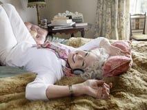 Senior Woman Listening Music In Bedroom Stock Photos