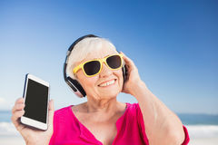 Senior woman listening music with headphone Stock Photos