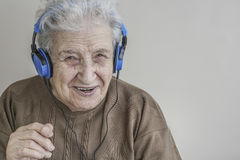 Senior woman listening music with headphones. A modern senior woman listening music with blue headphones Royalty Free Stock Images