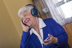Senior woman listening music. Senior woman listening music at home Royalty Free Stock Photos