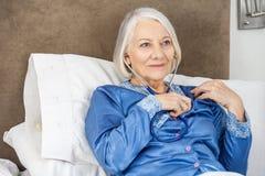Senior Woman Listening To Her Heartbeat Through Stock Photos