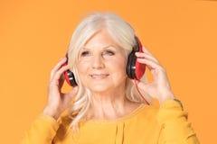 Senior woman listening to music royalty free stock photo