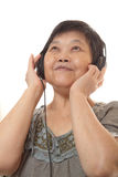 Senior woman listening to music with headphones Stock Photos
