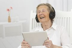 Senior woman listening to music on her tablet with headphones Stock Photo