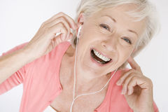 A senior woman listening to music on an mp3 player, laughing Stock Photo