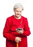 Senior woman listening to music over white Stock Images