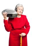 Senior woman listening to music on stereo recorder Royalty Free Stock Photography