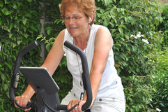 Senior woman listening to music during workout. Senior woman listening to favorite music during workout Royalty Free Stock Photography