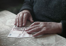 Senior woman with little euro money, toned image, colorized, selective focus, very shallow DOF Royalty Free Stock Image