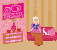 Senior woman in living room reading a book Stock Images