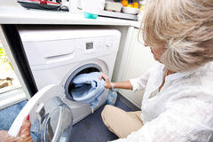 Senior woman loading towel in washing machine at home Royalty Free Stock Photo
