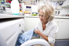 Senior woman loading washing machine at home Stock Photo