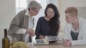 Senior woman with long black hair showing to friends her old photo album. Group of three middle aged mature women. Senior woman with long black hair showing to stock video