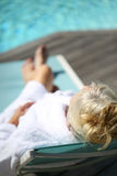 Senior woman in long chair by swimming pool Royalty Free Stock Photo
